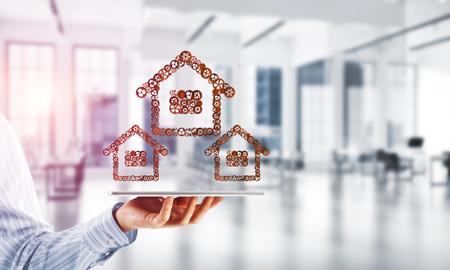 Sluit van tabletpc van de zakenmanholding met huisteken dat van verbonden toestellen wordt gemaakt. Gemengde media Stockfoto - 94298880