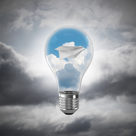 Glass lightbulb with flying paper plane and clouds inside with grey cloudly skyscape on background. 3D rendering.