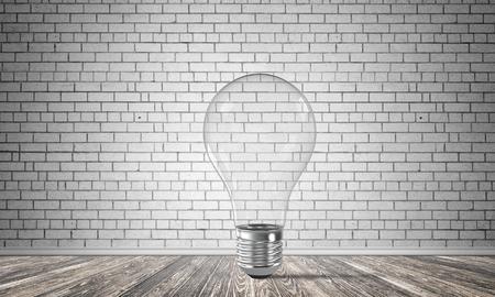 Transparant glas lightbulb in lege ruimte met grijze bakstenen muur op achtergrond. 3D-rendering. Stockfoto