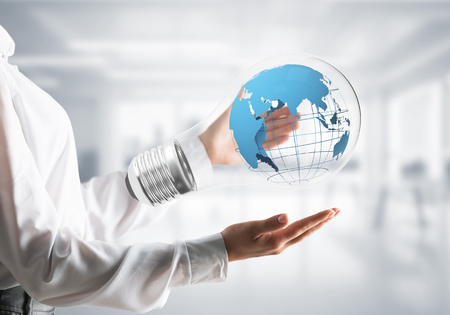 Cropped image of businessman in shirt holding lightbulb with Earth globe inside in hands with office view background.