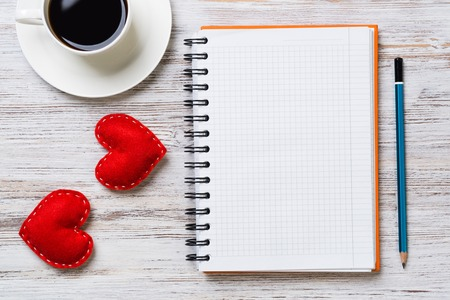 Coffee cup notepad pencil and two red hearts on wooden surface Stok Fotoğraf
