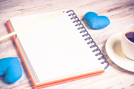 Coffee cup notepad pencil and two hearts on wooden surface