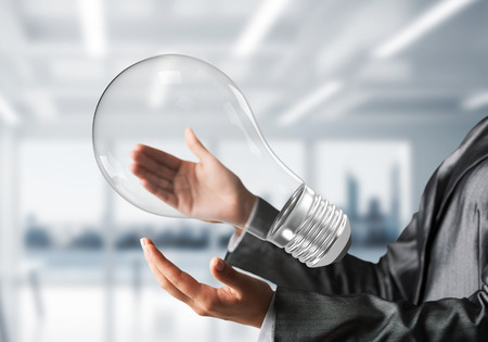 Closeup shot of business woman hands holding lightbulb. Sunlight on office view on background. Stock Photo