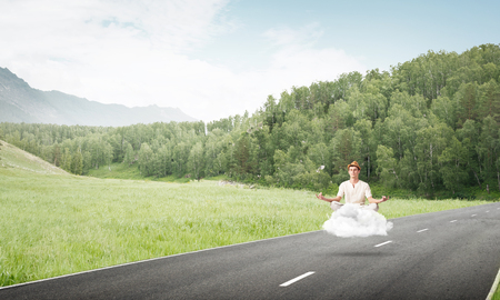 Young man keeping eyes closed and looking concentrated while meditating on cloud above the road with beautiful and breathtaking landscape on background. Stock Photo