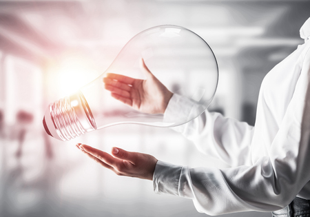 Closeup shot of business woman in white shirt holding lightbulb in hands with sunlight on office view background. Mixed media.