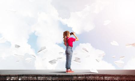 Leuk meisje van schoolleeftijd bij de bouw van dak die in verrekijkers kijken