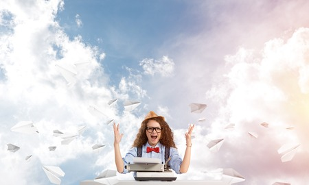 Young and beautiful woman writer in hat and eyeglasses using typing machine while sitting at the table among flying paper planes with cloudy skyscape on background.