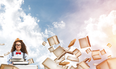 Young and beautiful woman writer in hat and eyeglasses using typing machine while sitting at the table among flying books with cloudy skyscape on background.