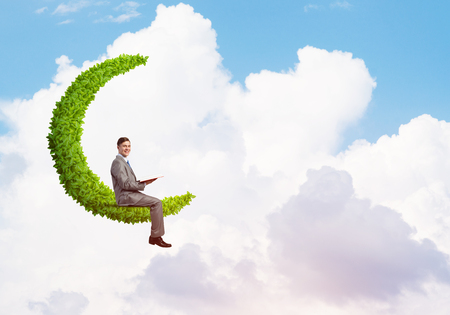 Young businessman floating on green moon in blue sky with red book in hands