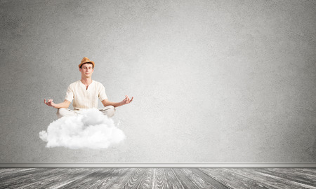 Young man keeping eyes closed and looking concentrated while meditating on cloud in the air with gray concrete wall on background.