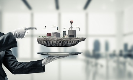 Cropped image of waitresss hand in white glove presenting modern city block on metal tray and pointing on it with office view on background. 3D rendering.