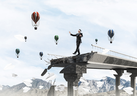 Businessman walking blindfolded among flying paper planes on concrete bridge with huge gap as symbol of hidden threats and risks. Flying balloons and nature view on background. 3D rendering.