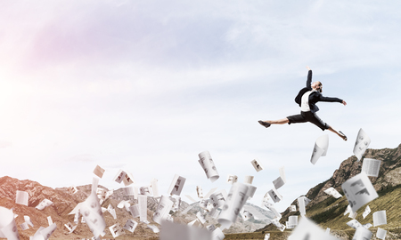 Attractive business woman in suit jumping in the air among flying papers as symbol of active life position. Skyscape and nature view on background. 3D rendering.