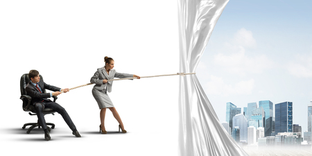 Two businesspeople pulling white blank fabric with rope Stock Photo