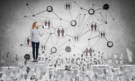 Woman in casual wear with speaker in hand standing among flying letters with social network structure on background. Mixed media.