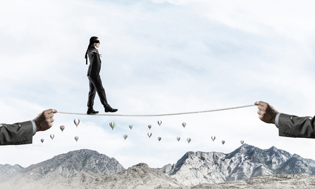 Businessman walking blindfolded on rope above high mountains as symbol of hidden threats and support. Flying balloons and nature view on background.