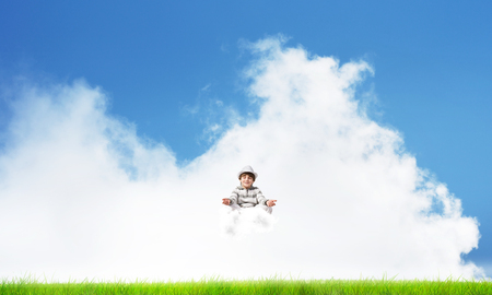 Young little boy keeping eyes closed and looking concentrated while meditating on cloud in the air with bright and beautiful landscape on background.