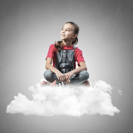 Cute kid girl sitting on cloud against concrete wall background