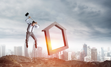 Jumping businessman crashing big house symbol with city view and sunlight on background. 3D rendering.