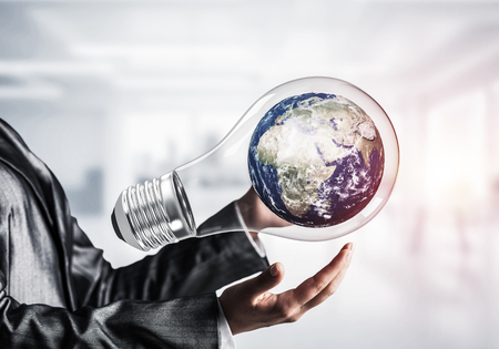 Closeup of business woman in suit holding in hands lightbulb with Earth globe inside. Sunlight on office view background. Elements of this image are furnished by NASA