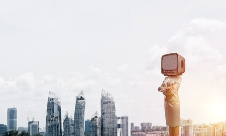 Cropped image of business woman in suit with old TV instead of head keeping arms crossed while standing outdoors with cityscape view on background. Banco de Imagens