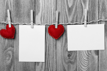 Blank sheet of paper hand made heart pinned to rope on wooden background Foto de archivo