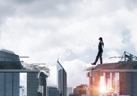 Businessman walking blindfolded on concrete bridge with huge gap as symbol of hidden threats and risks. Cityscape view with sunlight on background. 3D rendering. Stock Photo