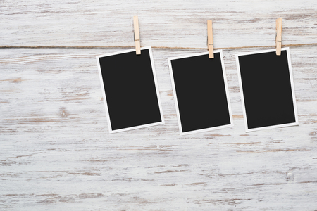 Blank photo frame hanging on rope on wooden textured background