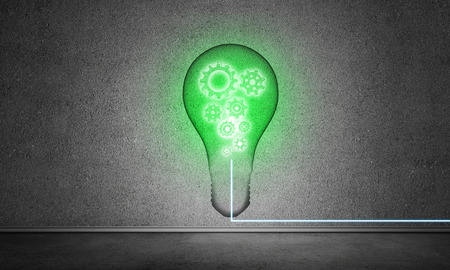 Green glass lightbulb with multiple gears inside placed in empty room with grey wall on background. 3D rendering. Stock Photo