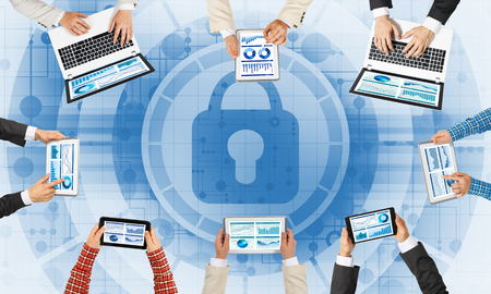 Group of people with devices in hands working together and symbol of net security and protection Foto de archivo