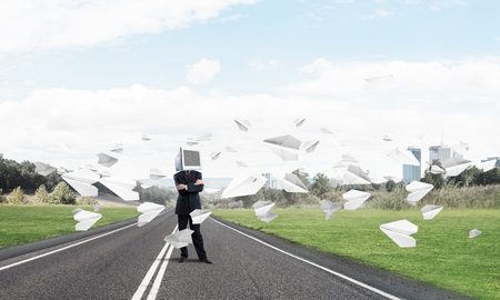 Businessman in suit with monitor instead of head keeping arms crossed while standing on the road among flying paper planes with beautiful landscape on background.
