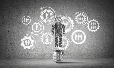 Lightbulb with human from gears inside placed against social gear structure on grey wall. 3D rendering.