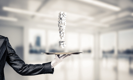 Cropped image of waitresss hand in white glove presenting multiple cubes in form of exclamation mark on metal tray with office view on background.
