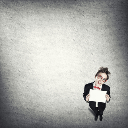 Top view of funny businessman holding blank paper sheet