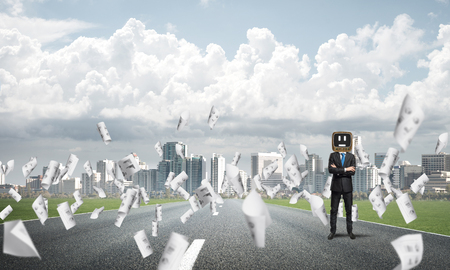 Businessman in suit with old TV instead of head keeping arms crossed while standing on the road among flying papers with beautiful landscape on background. Stock Photo