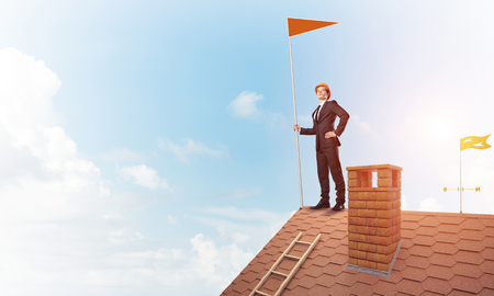 Businessman standing on house roof and holding red flag. Mixed media