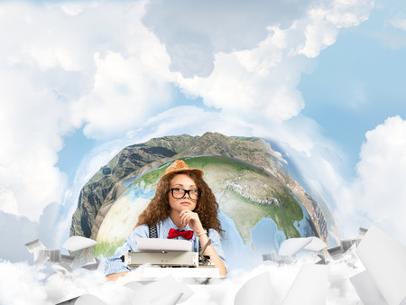 Portrait of thoughtful woman writer looking to camera and using typing machine while sitting at the table with flying papers and Earth globe among cloudy skyscape on background. Elements of this image furnished by NASA