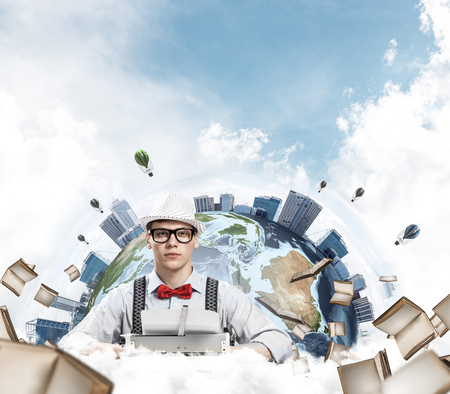 Young man writer in hat and eyeglasses using typing machine while sitting at the table with flying books and Earth globe among cloudy skyscape on background. Stock Photo