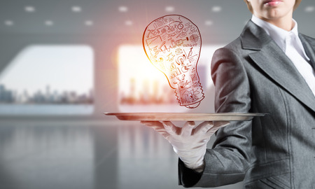 Closeup of waitresss hand in glove presenting sketched business plan in form of lightbulb on metal tray with office view on background.