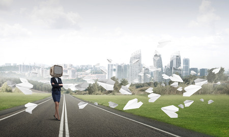 Business woman in suit with old TV instead of head keeping arms crossed while standing on the road among flying paper planes with beautiful landscape on background. Stock Photo