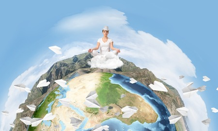 Young woman keeping eyes closed and looking concentrated while meditating on clouds in the air with panoramic view of Earth globe on background. Elements of this image are furnished by NASA