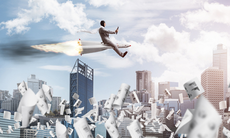 Conceptual image of young and happy businessman in suit flying on rocket among flying papers with modern cityscape with skyscrapers and blue sky on background. Stock Photo