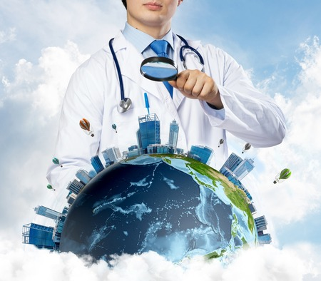 Conceptual image of confident doctor in white medical uniform looking on the Earth globe through loupe with cloudy skyscape on background. Medical industry concept.