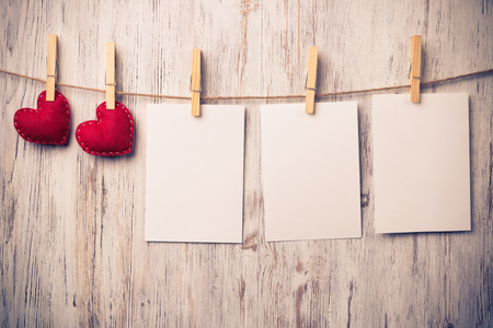 Blank sheet of paper hand made heart pinned to rope on wooden background Banco de Imagens