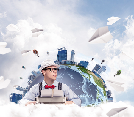 Portrait of handsome man writer in bow-tie and hat looking away while working with typing machine at the table with flying paper planes and Earth globe among cloudy skyscape on background.