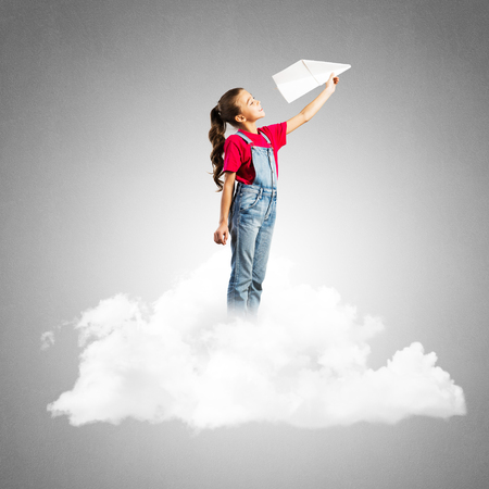 Cute kid girl standing on cloud and throwing paper plane Stockfoto