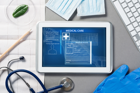 White tablet pc and doctor tools on gray surface Stock fotó