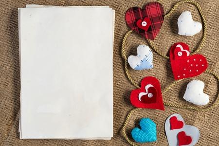 Handmade love hearts and sheets of blank paper  Фото со стока