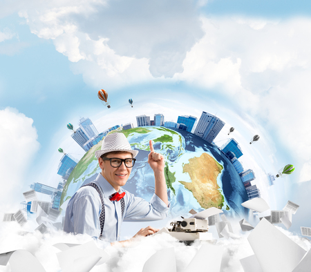 Young man writer in hat and eyeglasses pointing up while using typing machine at the table with flying papers and Earth globe among cloudy skyscape on background.