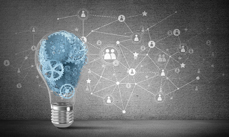 Lightbulb with multiple gears inside placed against social network system on grey wall. 3D rendering. Stock Photo